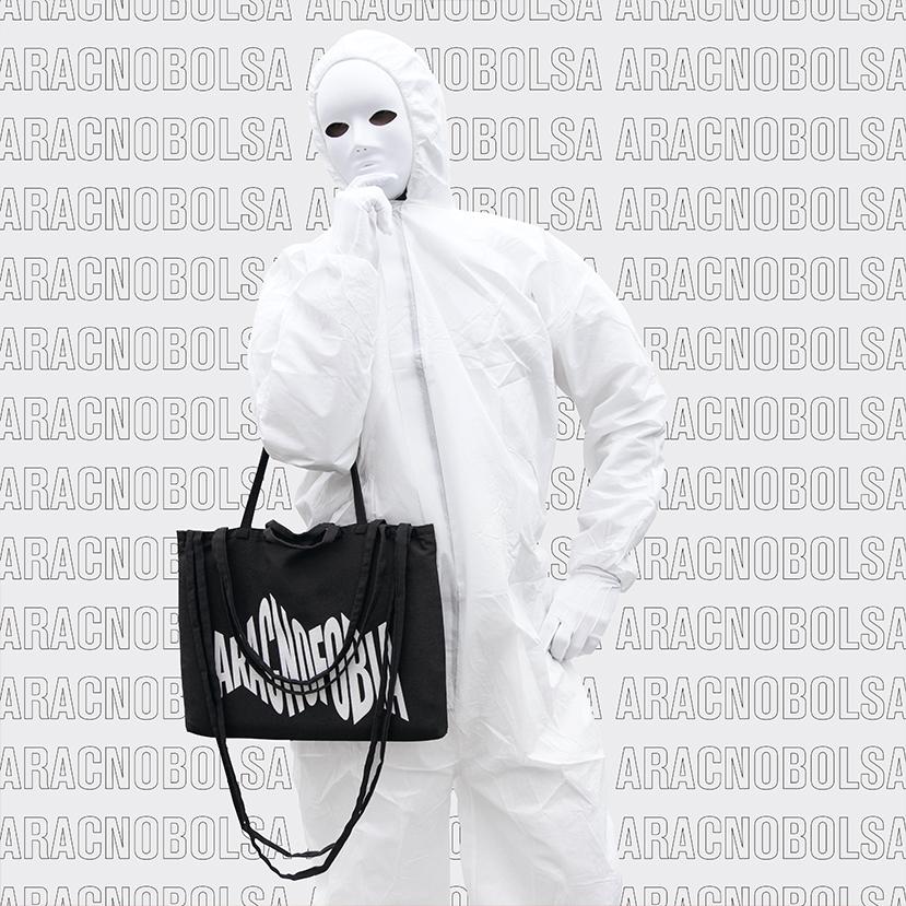 Una persona anónima vestida con mono blanco y máscara blanca sujeta con el brazo un bolso de 8 asas con el logo de Aracnofobia