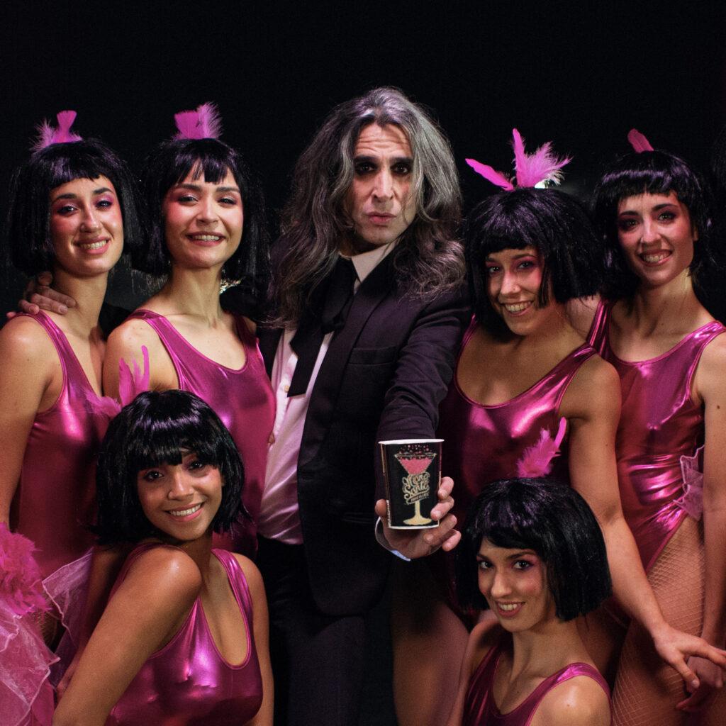 Mario Vaquerizo sostiene un envase de Mano de Santo rodeado por las bailarinas que representan las burbujas del producto.