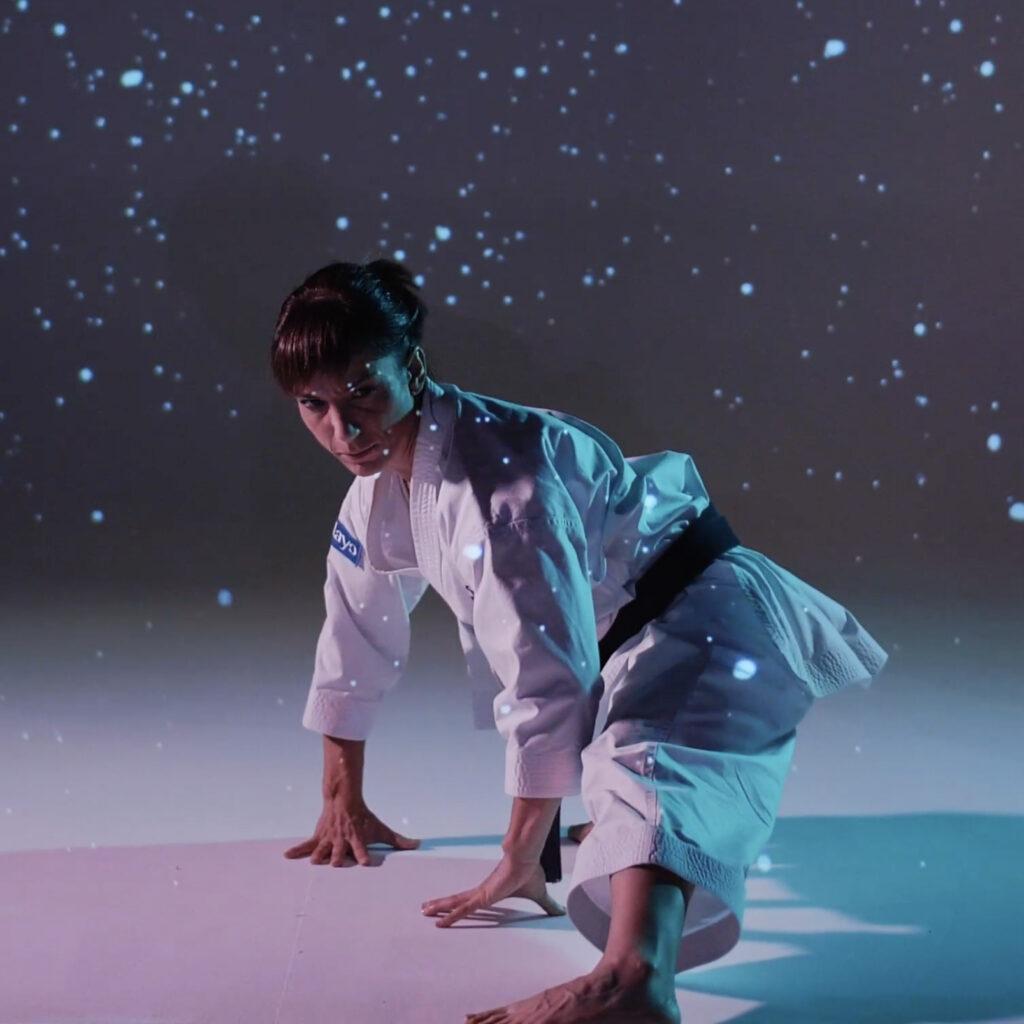 La karateka Sandra Sánchez realiza un movimiento de kata mientras se proyectan células sobre ella. Imagen del Kata contra el cáncer diseñado por Aracnofobia para Pelayo