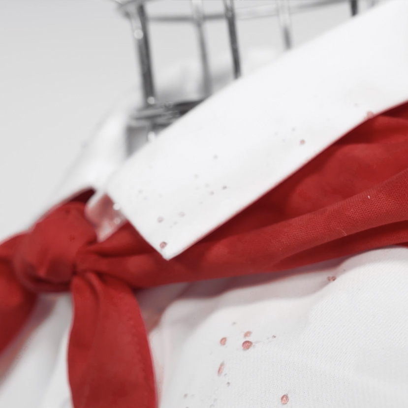 Detalle de cómo el vino resbala por el traje de Pamplonica que repele liquidos, diseñado por Aracnofobia para Mano de Santo.