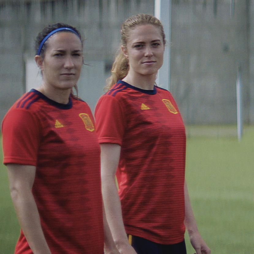 Dos jugadoras de la Selección femenina de futbol miran a cámara en un campo de fútbol.
