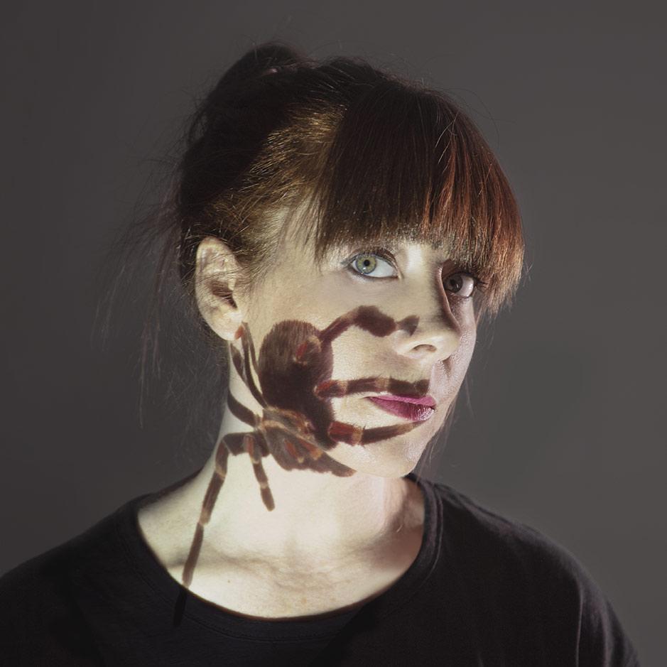 Retrato de Amabel Minchán con una proyección de una imagen de una araña proyectada sobre la cara.