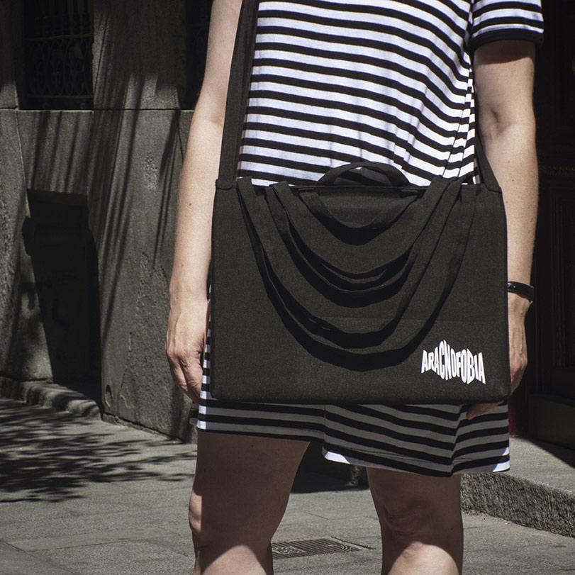 Chica con una bolsa de ocho asas con el logo de Aracnofobia colgada al cuello