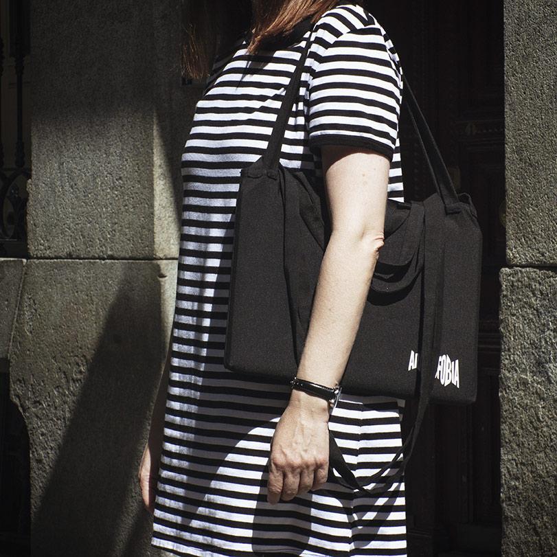 Chica con una bolsa de ocho asas con el logo de Aracnofobia colgada al hombro