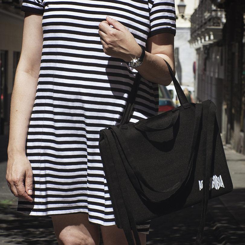Chica sujetando con el brazo una bolsa de 8 asas con el logo de Aracnofobia