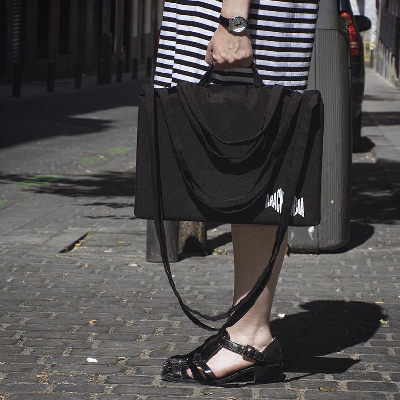 Chica sujetando con la mano una bolsa de ocho asas con el logo de Aracnofobia