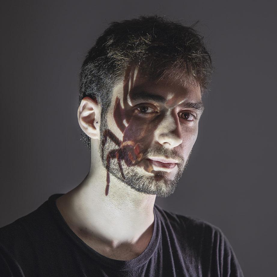 Retrato de Sergio con una proyección de una imagen de una araña proyectada sobre la cara.