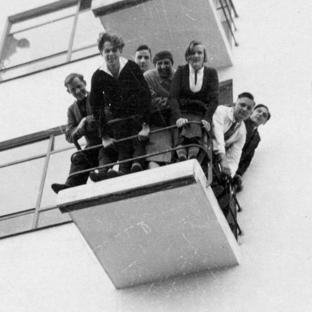 Miembros de la Bauhaus se asoman por un balcón del edificio de la escuela en Dessau.